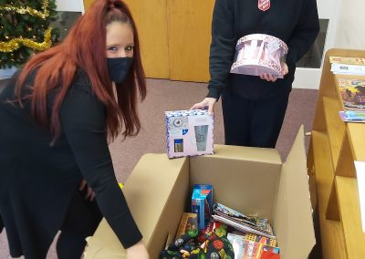 Our Sophie giving one of the boxes of toys and toiletries to Captain Wendy Hall at Heaton Norris Salvation Army Hall
